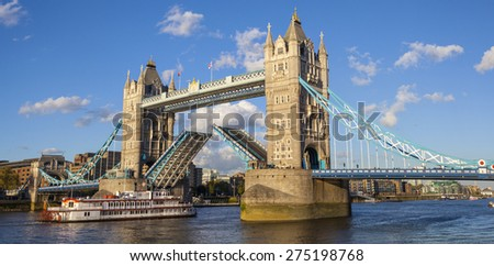 LONDON, UK - APRIL 29TH 2015: A panoramic view of Tower Bridge opening up over the River Thames to let a vessel pass underneath, on 29th April 2015. - stock photo