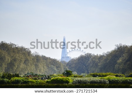 LONDON, UK - APRIL 22:  The Shard and London Eye seen from Kensington Gardens, framed by trees on a sunny spring day. April 22, 2015 in London. - stock photo