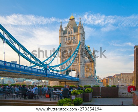LONDON, UK - APRIL15, 2015: Tower bridge in sunset. City of London, south bank of river Thames walk and small cafe. - stock photo