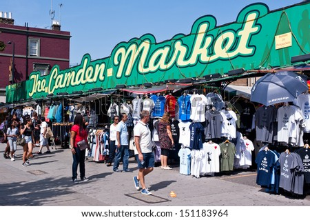 LONDON, UK - AUG 21: people walk past the Camden Market in London on August 21, 2013. Camden Town is London's most popular open-air market area with stalls, shops, pubs and restaurants. - stock photo