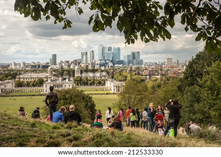 LONDON, UK - AUG 23: Visitors enjoy the view of the Canary Wharf skyscrapers from Greenwich park in London on August 23, 2014 - stock photo