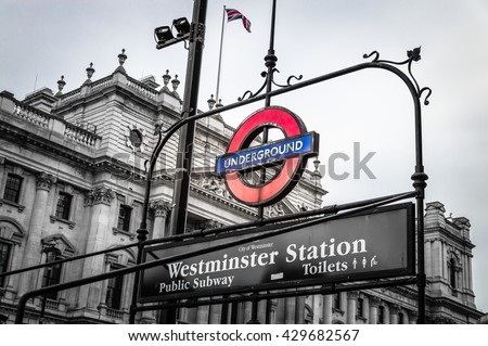 London, UK - August 18, 2015: London underground sign of Westminster station. The London Underground logo is one of the most recognised British icons. Black and white image with color sign