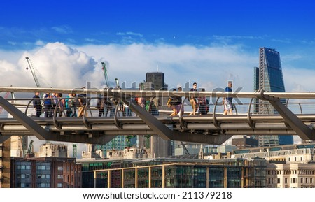 LONDON, UK - AUGUST 9, 2014: Millennium bridge next to St. Paul cathedral and Tate gallery with people crossing the river Thames