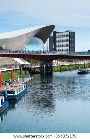 London, UK - August 2nd, 2015: photo of the Queen Elizabeth Olympic Park, with the London Aquatics Center and people crossing over the bridge in the background.
