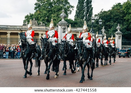 London, UK - August 19, 2015: Queen's Guards cavalry parade during traditional Changing of the Guards ceremony at Buckingham Palace. This is one of the most popular tourist attractions in London. - stock photo