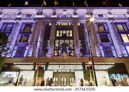 LONDON, UK - AUGUST 8: Selfridges Department Store facade in Oxford Street illuminated at night with people passing, central London on August 8 2015. The street is famous for luxury fashion shops.