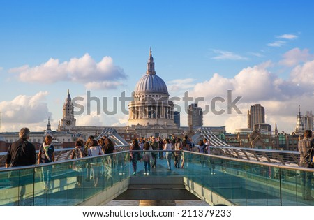 LONDON, UK - AUGUST 9, 2014:  South bank walk of the river Thames. St. Paul's cathedral. View on bridge and modern architecture