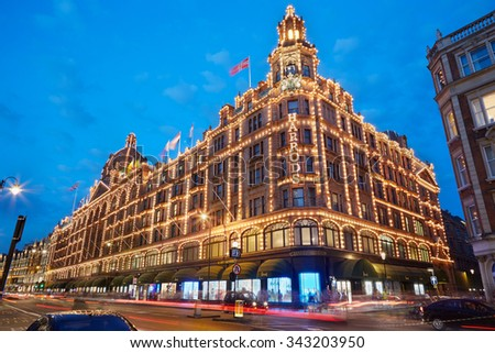 LONDON, UK - AUGUST 8: The famous Harrods department store illuminated in the evening of August 8, 2015 in London, UK. Harrods is the biggest department store in Europe. - stock photo