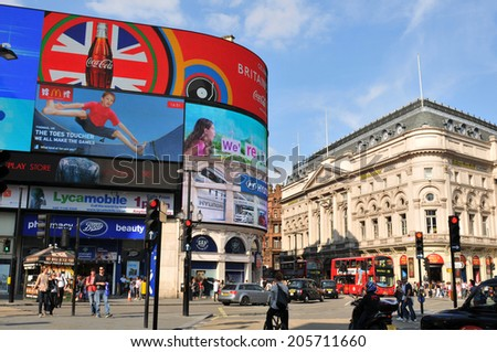 LONDON, UK - AUGUST 9, 2012: Tourists visit Piccadilly Circus, major commercial area of London, home of important landmarks and shops. - stock photo