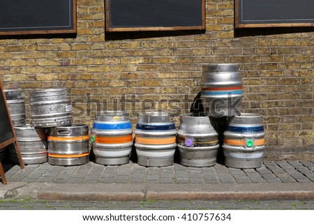 London,UK. 04.04.2016. Colorful kegs of beer at the exit of a pub, on a brick wall - stock photo