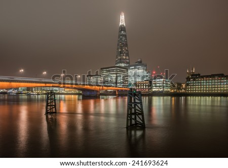 LONDON, UK - DEC 1: London skyline at night including The Shard skyscraper, London Bridge and illuminated buildings under thick clouds in London on December 1, 2014 - stock photo