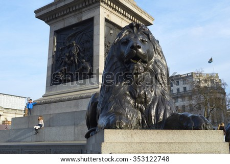 LONDON, UK - DECEMBER 19: Detail of one of the four lions statues that surround Nelson's Column in Trafalgar Square, with children seated in the background. December 19, 2015 in London. - stock photo