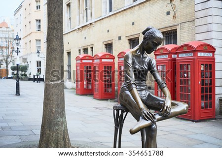 LONDON, UK - DECEMBER 20: Young Dancer statue, by Enzo Plazzotta, with line of red phone booths in the background. December 20, 2015 in London. - stock photo