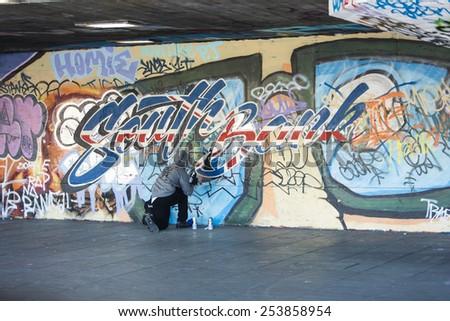 LONDON, UK - FEB 2015 - London Southbank Skate park as a graffiti artist finishes off latest design - stock photo