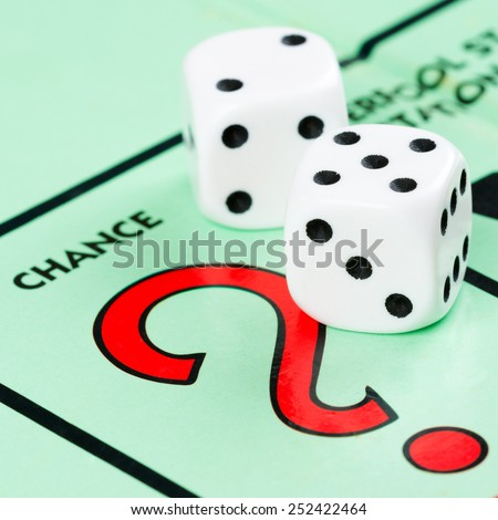 LONDON,UK - FEBRUARY 11, 2015 : Pair of dice next to the CHANCE card drawing space in a Monopoly game board - stock photo