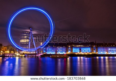 LONDON UK - JANUARY 26, 2013: A view of the  EDF Energy London Eye, commonly referred to as the London Eye or the Millennium Wheel, and County Hall with the River Thames in the foreground.  - stock photo