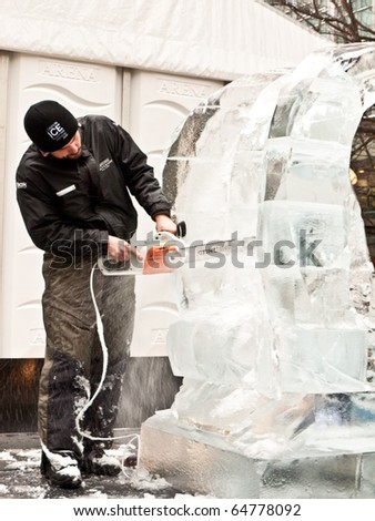 LONDON, UK - JANUARY 15: Ice Sculptor at Work With Power Tool at the Annual London Ice Sculpture Festival Competition.Canary Wharf, London January 15 2010 - stock photo