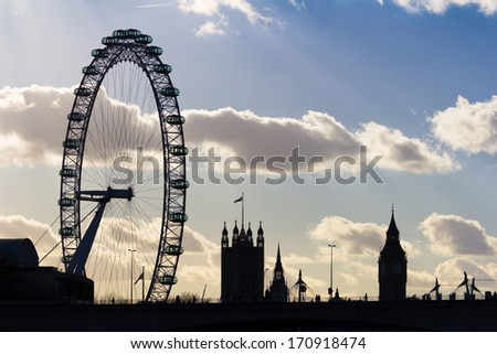 LONDON, UK - JANUARY 11, 2014: The London Eye and Big Ben at Sunset from the other side of Waterloo Bridge - stock photo