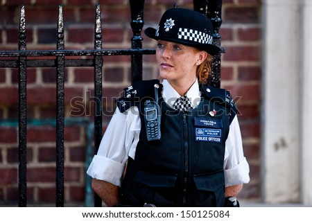 LONDON, UK - JUL 22: a woman police officer guards the entrance of St. Mary's Hospital in London on July 22, 2013 on the day the Royal Baby is born. - stock photo