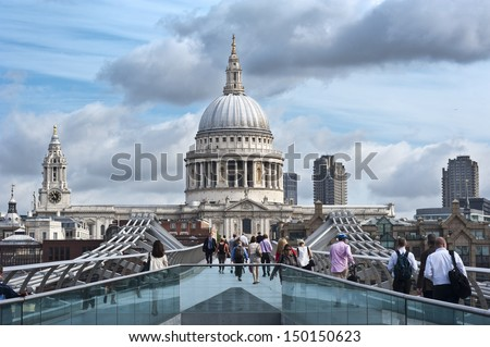 LONDON, UK -  JUL 1: commuters walk across the Millennium Bridge in London on July 1, 2013. On the background is St Paul's Cathedral. The bridge was opened on June 10, 2000.