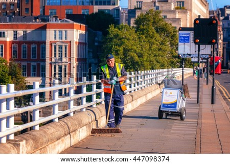 LONDON, UK - JULY, 03, 2016: A street sweeper walks along a city centre road. Westminister City Council employ street sweeping and refuse collection services throughout the west country city.