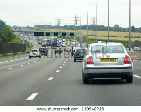 LONDON, UK - JULY 20: Heavy traffic on british motorway M1 on July 20, 2012, London, UK. The M1 is a north-south motorway in England connecting London to Leeds. The motorway is 193 miles / 311km long. - stock photo