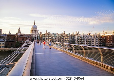LONDON, UK - 19 JULY: People walking on the Milennium Bridge to and from St Pauls Cathedral , on 19n july at sunset in London, UK.