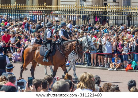 LONDON, UK - JULY 21, 2015: Police officers on controlling crowds in front of Buckingham palace in London, England. - stock photo