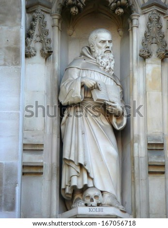 LONDON, UK - JULY 6: Statue of saint Maximilian Kolbe from facade of Westminster Abbey on July 6, 2013 in London. Westminster Abbey is UNESCO World Heritage Site. - stock photo