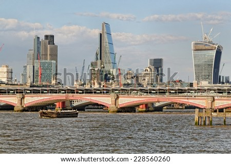 LONDON, UK- July 1: Thames embankment on July 1, 2014 in London, UK. The City of London skyline at daytime.
