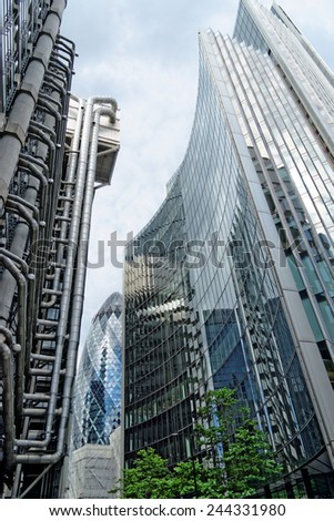 LONDON, UK - JULY 1, 2014: The famous office buildings - The Willis and the Lloyds building the Gherkin Tower in the distance in the City of London, one of the leading centers of global finance