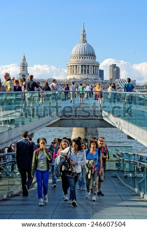 LONDON, UK - JULY 1, 2014: Tourists crossing the Millennium Bridge linking the City of London with the South Bank between St Paul Cathedral and Tate Modern art gallery. - stock photo