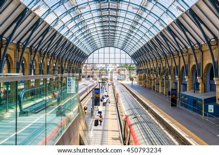 London, UK - July 5, 2016 - Travellers pass along platforms in Kings Cross train station - stock photo