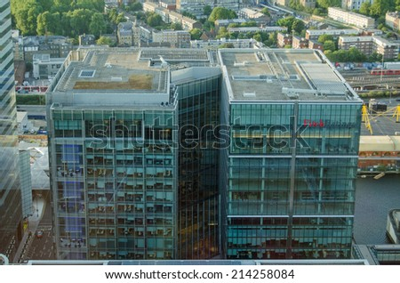 LONDON, UK  JULY 1, 2014:  View from an even taller building of the Fitch Ratings headquarters offices in the Canary Wharf district of London Docklands. - stock photo