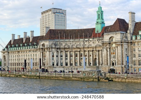 LONDON, UK - JULY 1, 2014: View of London County Hall and Aquarium. The Aquarium is located on ground floor of County Hall on South Bank of River Thames and hosts about one million visitors per year. - stock photo