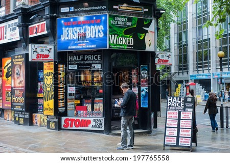 LONDON, UK - 7 JUN: Tourists stand in front of a booth selling tickets for musical and theatre shows in London on 7 June 2014. - stock photo