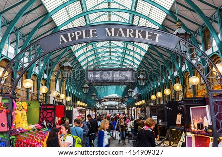 London, UK - June 16, 2016: Apple market in the market hall at Covent Garden with unidentified people. The historic hall is today a tourist location containing cafes, pubs, shops, and two markets