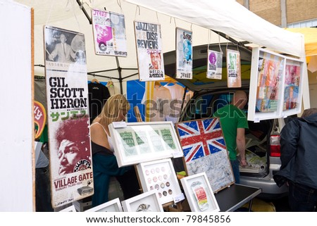 LONDON, UK- JUNE 19: Artist Swifty shows prints and art work on his stall at the Annual Art Car Boot Fair in London's East End on June 19, 2011 in London UK. - stock photo