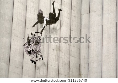 LONDON, UK - JUNE 15, 2015:  Banksy graffiti on the side of a disused office block in Central London showing a woman shopper falling with her shopping trolley.  On public display viewed from pavement. - stock photo