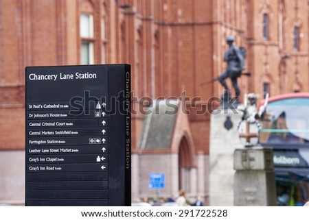 LONDON, UK - JUNE 23: Chancery Lane Station direction sign with war memorial in the background. June 23, 2015 in London. - stock photo