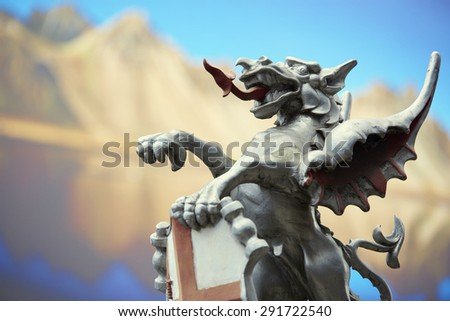 LONDON, UK - JUNE 23: Detail of the City of London dragon with photograph of mountains in the background. June 23, 2015 in London. - stock photo