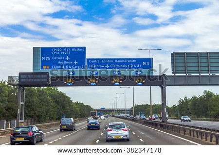 LONDON, UK - JUNE 5, 2015: Intensive left-hand traffic on British four lane motorway M4 between Windsor and London  with active electronic overhead information sign at grey cloudy  summer day