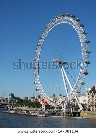 LONDON, UK - JUNE 26: London Eye and Thames river on June 26, 2011 in London, UK. The London Eye is a giant Ferris wheel on the South Bank of the River Thames in London, England.  - stock photo