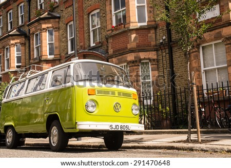 London, UK - June 06 2015: Old vintage green van parked in a street with victorian houses in the background - stock photo