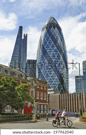 LONDON, UK- JUNE 06: The modern glass buildings of the Swiss Re Gherkin on June 06, 2014 in London, England. This tower is 180 meters tall and stands in the City of London Financial District. - stock photo