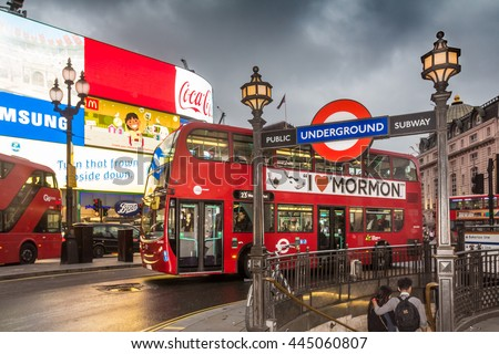 LONDON, UK - JUNE 28, 2016:  Tourists enter the London Underground subway by the neon-lit Piccadilly Circus at dusk