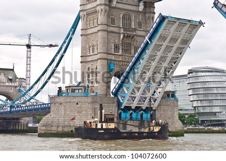 LONDON, UK-JUNE 1: Vic 96 ex Admiiralty victualling inshore craft,supplied the Fleet in World War II, sails under Tower Bridge for the Queen's Diamond Jubilee pageant. June 1, 2012 in London UK - stock photo