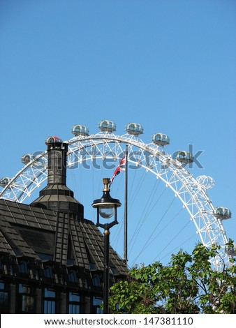 LONDON, UK - JUNE 26: View of black roof, street lamp, britain flag and famous London Eye on June 26, 2011 in London, UK. The London Eye is the the most popular tourist attraction in the UK. - stock photo