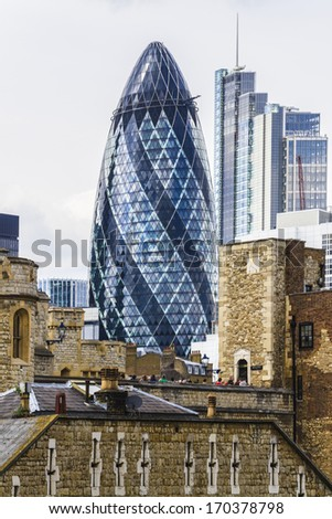 LONDON, UK - JUNE 3, 2013: View of Gherkin building (30 St Mary Axe) and Tower of London Walls - historic castle on north bank of River Thames. Gherkin skyscraper - iconic symbol of London. - stock photo