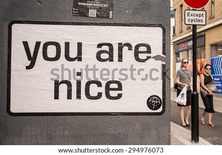 "London, UK - June 28 2015: White billboard with the words ""You are nice"" on a wall in a street in London. Two woman with sunglasses walking next to it."